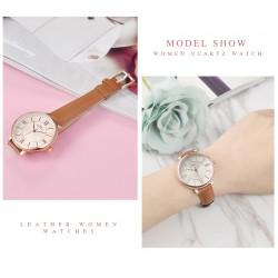 Stylowydamski zegarek na pasku z tarczą i skórzanym paskiem w kolorzebrązowyoraz kopertą w kolorze złotym. -
